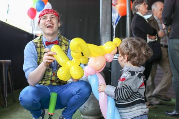 balloon twister smiling while handing child balloon