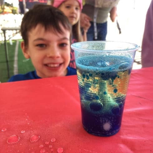 A boy watches a lava lamp experiment bubble at a children's science party