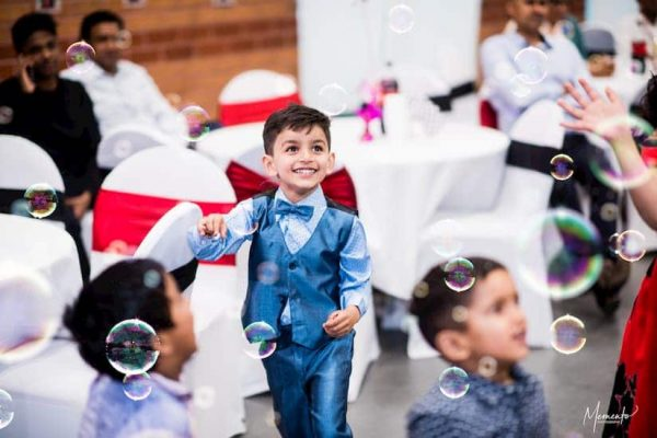 Child smiling while dancing with bubbles